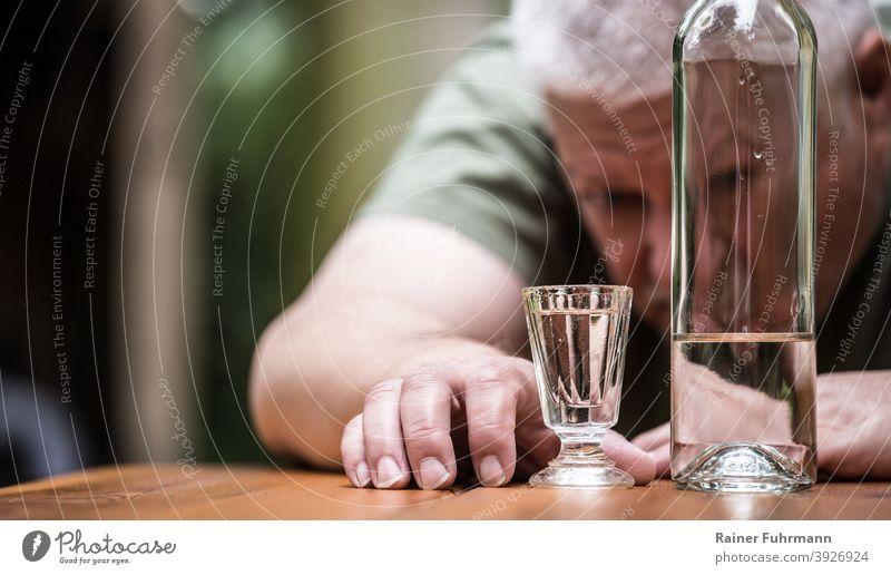 Ein Mann starrt auf sein volles Schnapsglas, daneben steht eine Flasche mit Alkohol Alkoholiker Wodka Glas trinken Getränk Alkoholsucht Farbfoto Spirituosen