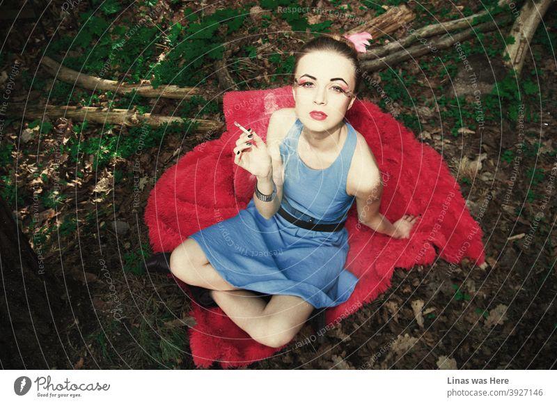 Diese Waldfee mit einer süßen Zigarette in der Hand und einem glänzenden blauen Kleid ist eine Versuchung, der man nicht widerstehen kann. Wunderschönes Model mit roten Lippen und schönem Make-up starrt direkt in die Linse. Modische Schönheit.