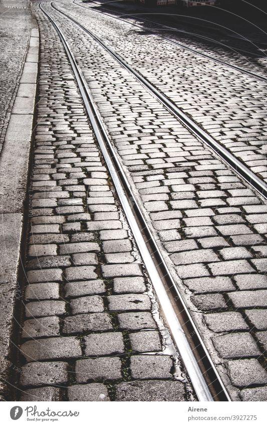 immer den Schienen nach Straße Kopfsteinpflaster Straßenbahnschienen geradeaus Zielgerade menschenleer grau gepflastert sonnig Fußgängerzone Pflastersteine