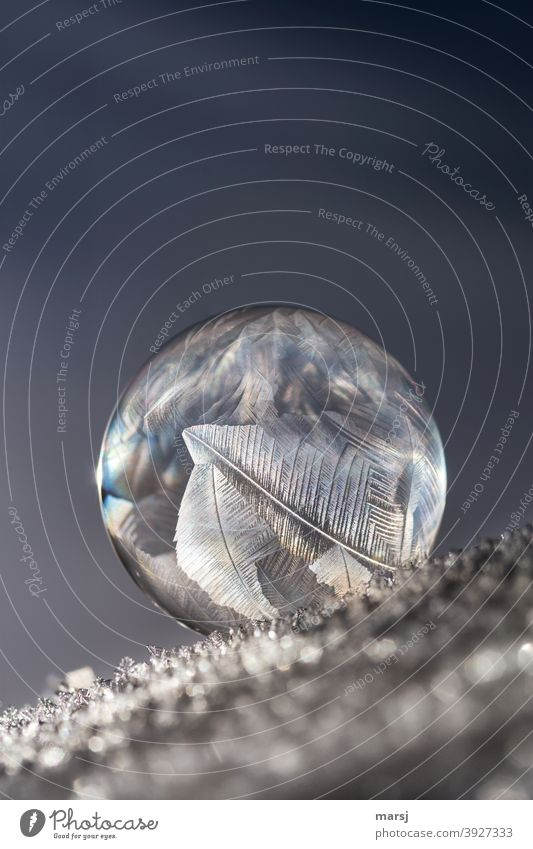 Eingebildete und aufgeblasene Kugel,  die auf die schiefe Bahn geraten ist.. Eisstrukturen auf einer Seifenblase. Vergänglichkeit einzigartig bizarr Reinheit