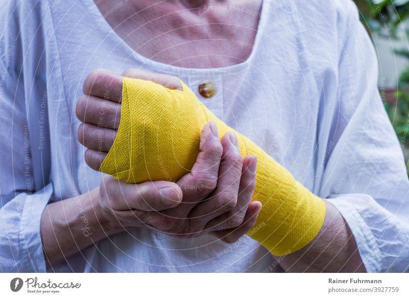 Eine Frau hat eine Verletzung am Handgelenk, sie trägt einen gelben Verband Gesundheit Krankheit Arbeitsunfall Arbeitsausfall Krankenversicherung Person
