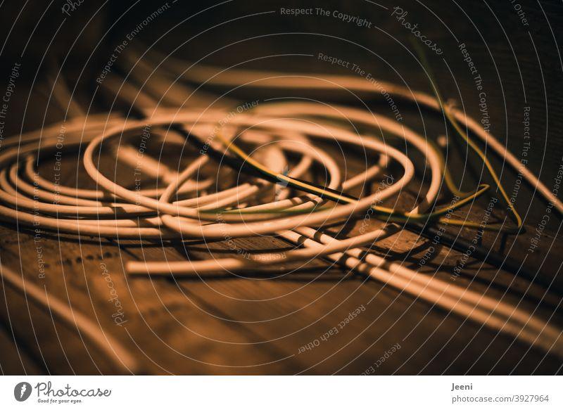 Auf dem Holzfußboden liegt ein Durcheinander von Kabeln Kabelsalat Stromkabel Technik & Technologie Elektrizität durcheinander Leitung Leitungen Energie