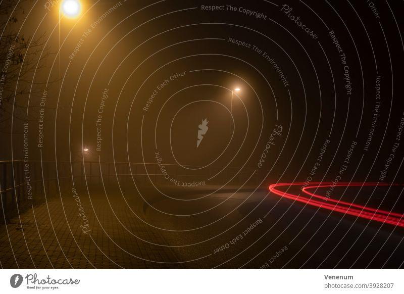 Lichtspuren von Autos im Nebel bei Nacht PKW Lastkraftwagen Scheinwerfer Straße Autobahn Baum Bäume Himmel Abend Blinker Rückleuchten rot weiß Wegweiser