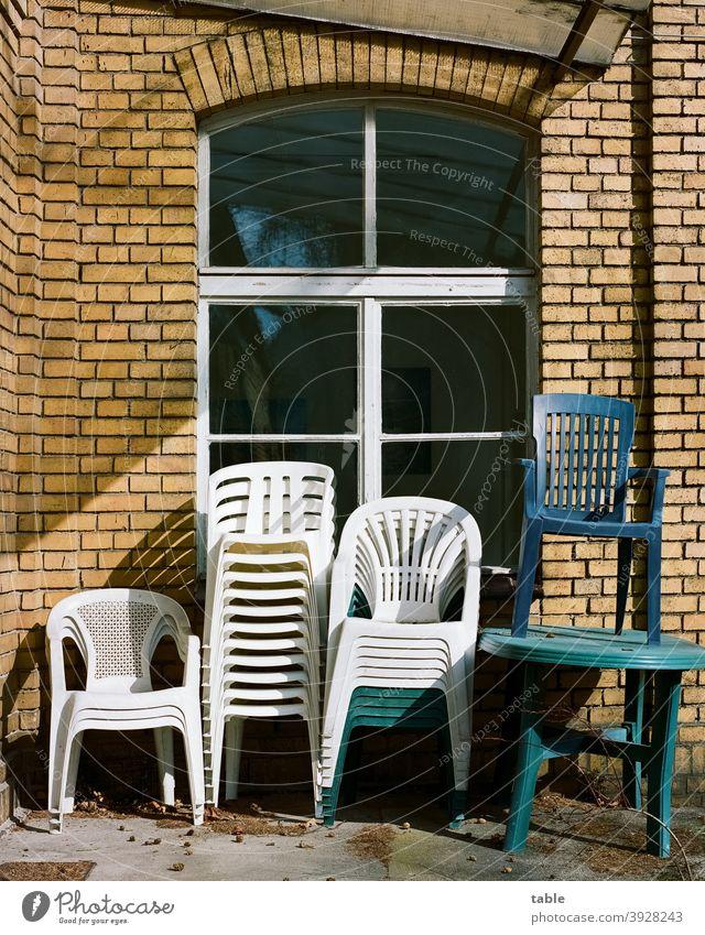 mehrere Stapelstühle aus Kunststoff stehen übereinandergestapelt an einer Hauswand Stuhl Sonnenlicht Außenaufnahme Farbfoto Ordnung Erholung ruhig geduldig