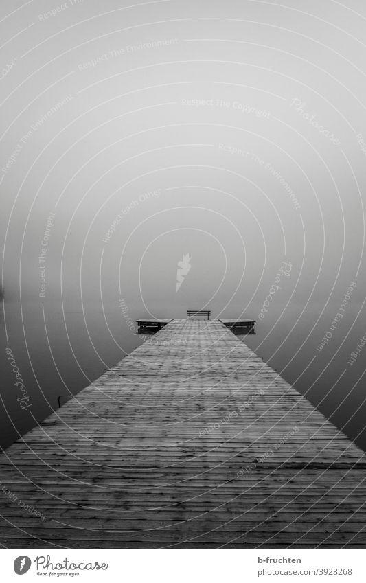 Nebeltag am See, Holzsteg mit Parkbank am Ende Wasser Steg Herbst lang Mitte leer kalt Schwarzweißfoto ruhig Natur Landschaft Seeufer Morgen Einsamkeit Stimmung