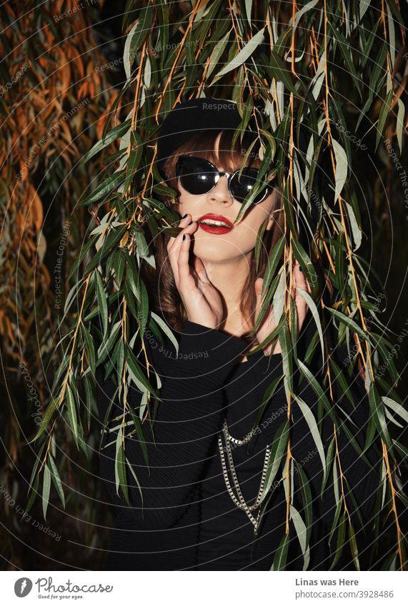 Dieses wunderschöne brünette Mädchen mit Sonnenbrille wurde an einem perfekten Herbstnachmittag aufgenommen. Sie ist in schwarz gekleidet und hat offensichtlich einen Geschmack für Mode. Rote Lippen passen gut zu gelben Herbstblättern.