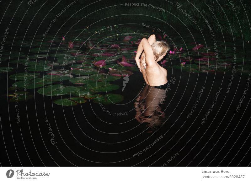Dieses dunkle Wasser hält nackte Mädchen nicht davon ab, darin zu schwimmen. Ein perfektes blondes Model mit einem perfekten Körper hat Spaß in einer heißen Sommernacht. Seerosen, sexy Kurven und eine absolut kühle Atmosphäre in diesem Bild.