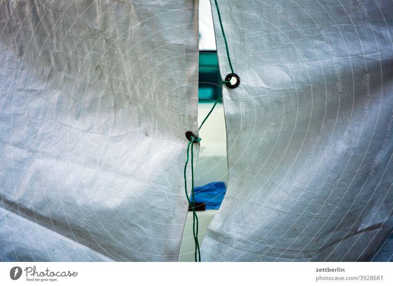 Schlitz in einer Plane schlitz lücke plane decke verdecken abdeckung sicherung kauschen öse verbindung schnur faden strick leine verbinden durchsicht neugier