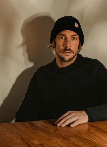 Portrait eines jungen Mannes portrait junger mann mütze pullover ehrlich atmosphärisch holztisch bart Oberlippenbart aufrichtig modern modisch natürlich
