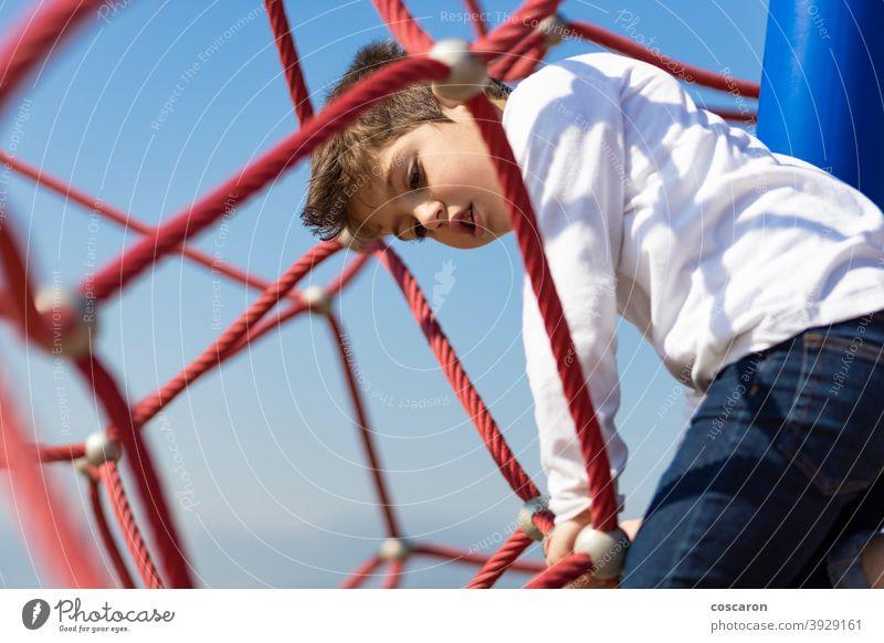 Lustiger Junge beim Klettern auf einem Spielplatz aktiv Aktivität Abenteuer Gleichgewicht Blauer Himmel Mut Kaukasier Kind Kindheit Kinder Klettergerüst Farbe
