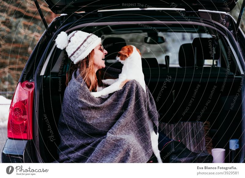 Junge Frau und niedlichen Jack Russel Hund im Auto. Wintersaison, verschneiten Berg Hintergrund Decke Natur Zusammensein Saison Fernweh Schönheit aktiv