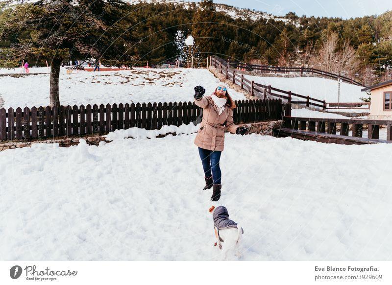 Frau und niedlichen Jack Russell Hund genießen draußen am Berg mit Schnee. Wintersaison Berge u. Gebirge im Freien reisen Lifestyle Fernweh reisend Spaß kalt