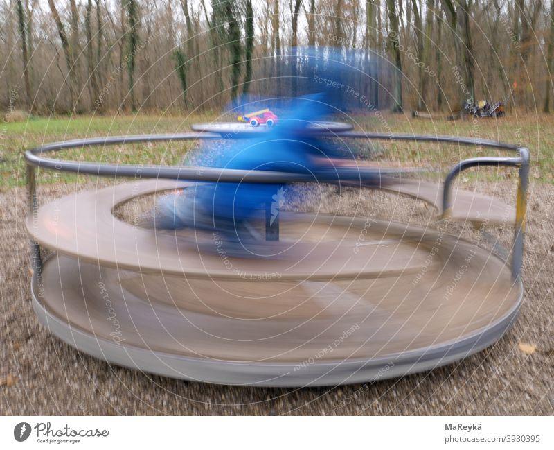 Kind dreht sich auf Drehscheibe auf dem Waldspielplatz und bekommt einen Drehwurm Drehen Feuerwehrauto Spielen Spielplatz Langzeitbelichtung Kindheit Bewegung