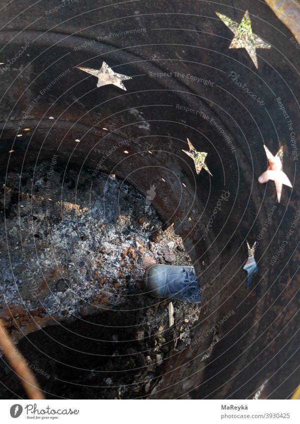 Sternenhimmel in der Feuertonne mit Kinderfuß Asche Kinderschuhe Fuß Rost rostig