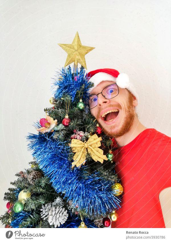 Foto eines lächelnden Jungen mit Weihnachtsmannmütze an der Seite eines Weihnachtsbaums Weihnachten Dekoration & Verzierung Gesicht Feiertag männlich rot