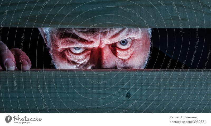 Ein Mann blickt böse durch eine Lücke in einer Holzwand Blick Nahaufnahme intensiv Porträt Gesicht Mensch Auge dunkel schwarz Angst Freak verrückt eingesperrt