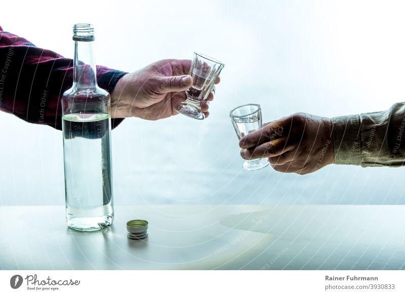 Auf einem Tisch steht eine Flasche mit Alkohol. Die Hände von zwei Männern halten Schnapsgläser. Sie stoßen miteinander an. Alkoholismus Sucht Feier feiern