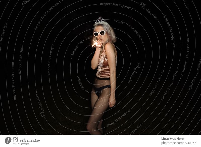 Es ist Party-Zeit und diese wunderschöne blonde Mädchen ist alles über Spaß zu haben. Gekleidet in schwarze Dessous und eine glänzende Tiara mit Sonnenbrille ist sie bereit zu feiern. Dunkelheit ist alles um und nur der Blitz offenbart die Geheimnisse der Nacht.