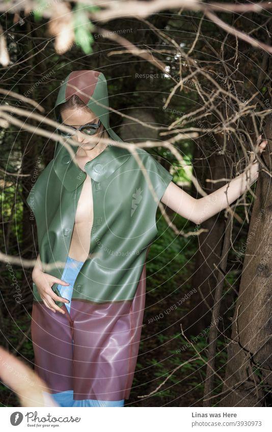 Ein wunderschönes Modemodell posiert in einem dunklen Wald. Sie ist mit einem bunten Regenmantel bekleidet. Ein modisches Mädchen mit sexy Kurven und Sonnenbrille ist in diesem stimmungsvollen Wald verloren.