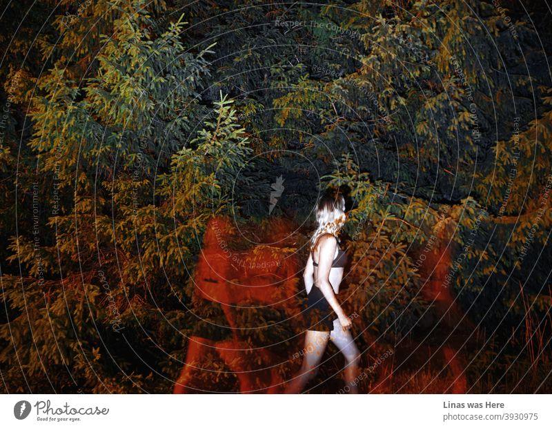 Dunkle Schatten mit roten Lichtern folgen diesem hinreißenden blonden Mädchen. Das Dessous-Modell ist in schwarzen Shorts und einem Bikini gekleidet. Sie läuft vor unsichtbaren Geistern davon. Das Ganze spielt sich in einem dunklen Wald ab.