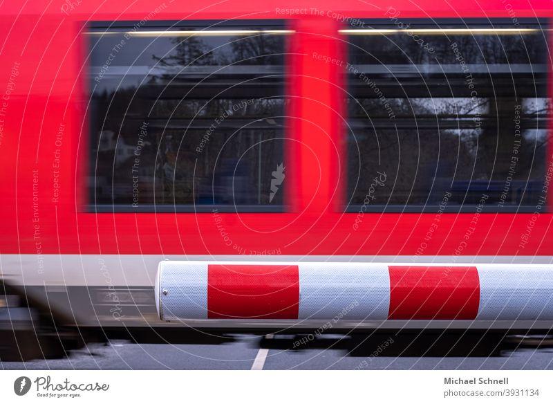 Zugschranke geschlossen und vorbeifahrender Zug Schranke schrankenbaum warten wartend schnell Bahn Verkehr Eisenbahn Geschwindigkeit Bewegung rot-weiß