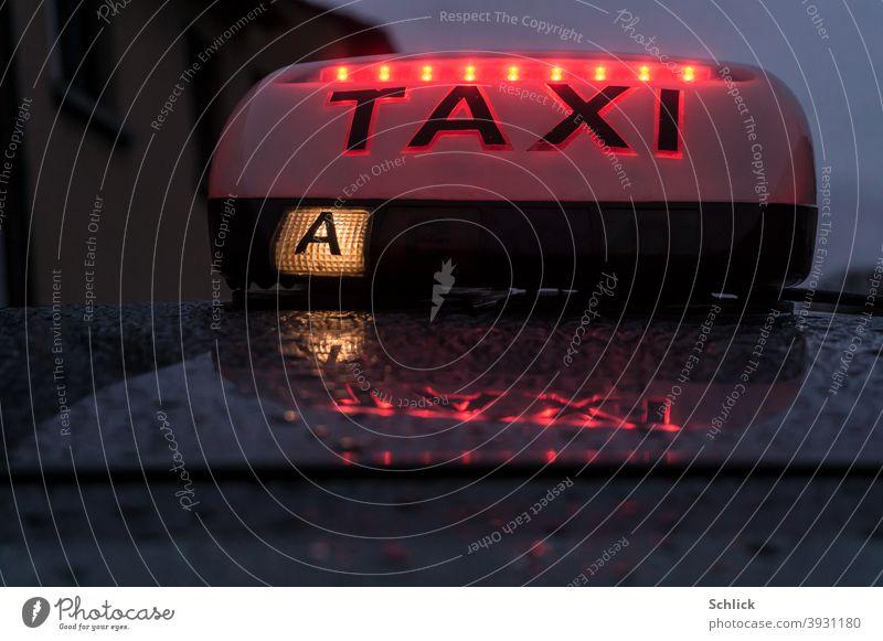 Leuchte auf einem Taxi mit roten LEDs und Spiegelung im regennassen Blechdach Taxileuchte Dämmerung Regentropfen Wassertropfen A Frankreich Lothringen
