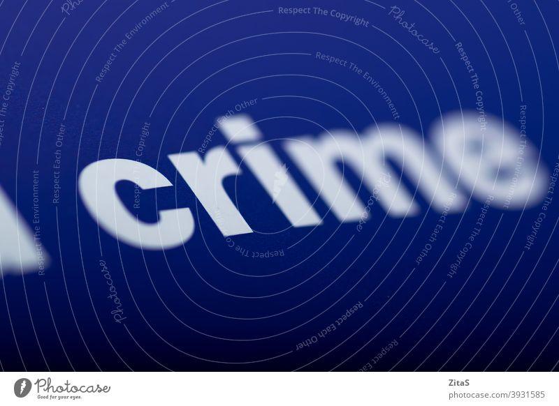 Verbrechenswort vor blauem Hintergrund getippt Wort Nahaufnahme Blauer Hintergrund Buch Makro Text Page