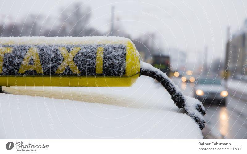 Ein Taxi steht in einer Stadt am Strassenrand. Es ist ein trüber Wintertag, es liegt etwas Schnee. Verkehr Außenaufnahme Verkehrsmittel Straße Verkehrswege