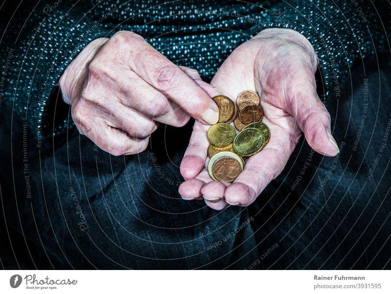 eine ältere Frau hält in ihren Händen wenige Münzen alt faltig Rentner Rentnerin Rente Armut Geld Hartgeld sparen Sparsamkeit Geldanlage Bargeld Euro Finanzen