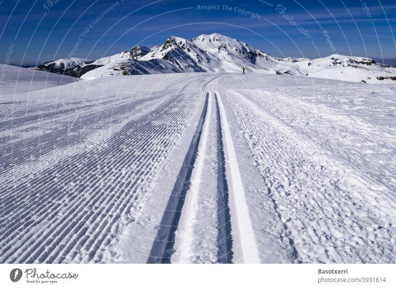 Gespurte Skilanglaufpiste in den Bergen. Kleine Person (Skilangläuferin) im Hintergrund. Isaba/Belagua, Navarra in den spanischen Pyrenäen. Skipiste Spur