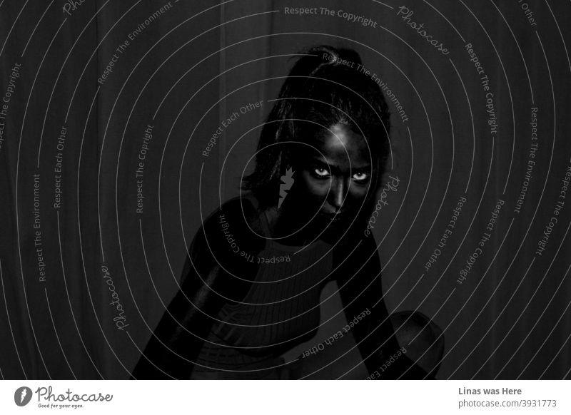 Es ist überall dunkel und zwei Augen starren direkt in die Kamera. In dieser Dunkelheit kann man das dunkelhäutige weibliche Model, das ganz in Schwarz gekleidet ist, kaum erkennen. Selbst die Schatten sind dunkler als sonst.