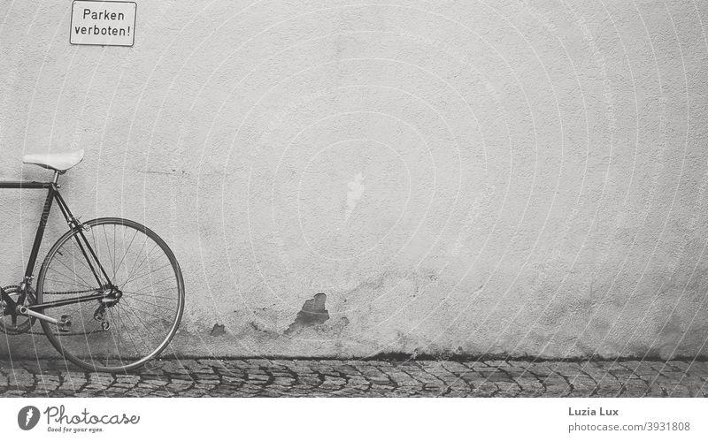 Parken verboten, dazu Hinterrad, Pedal und Sattel eines Fahrrads und altes Kopfsteinpflaster parken verboten Hinweisschild Hauswand Schilder & Markierungen