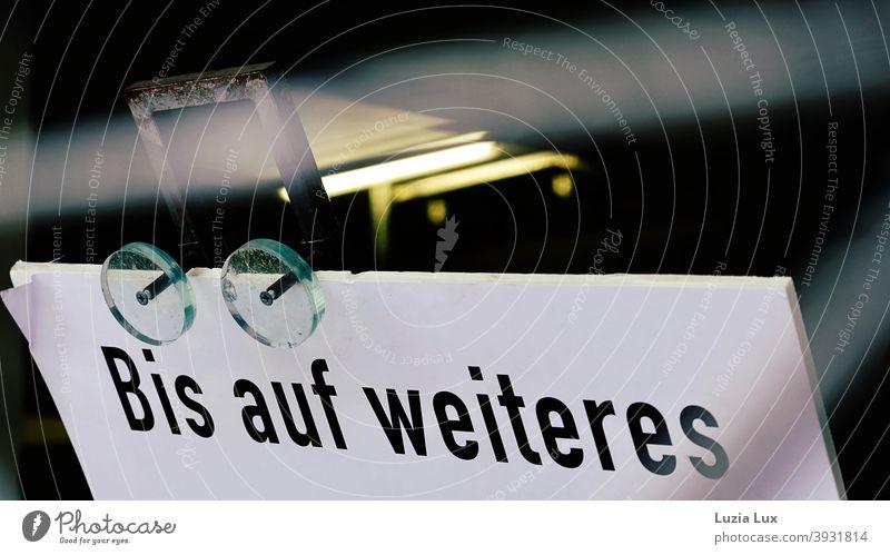 Bis auf Weiteres... Teilansicht eines Schildes, darüber Neonlicht Schilder & Markierungen geschlossen Schrift Licht Hinweisschild Buchstaben Menschenleer