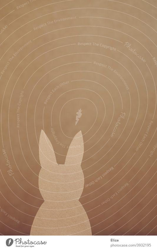 Hase aus Papier vor braunem Hintergrund. Ostern. basteln Silhouette Scherenschnitt Osterhase Tier Hasenohren Osterdekoration