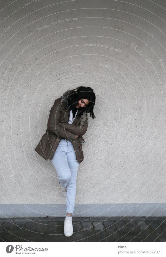 Elis frau wand stehen nachdenklich angelehnt jacke jeans schwarzhaarig langhaarig sneakers mauer lächeln glücklich
