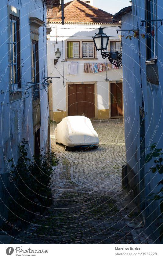 Anonymes Auto in einer engen Kopfsteinpflasterstraße. anonym leer PKW unten Deckung Bauplane Zeltplane alt Straße gepflastert weiße Häuser Wäschelinie Laternen