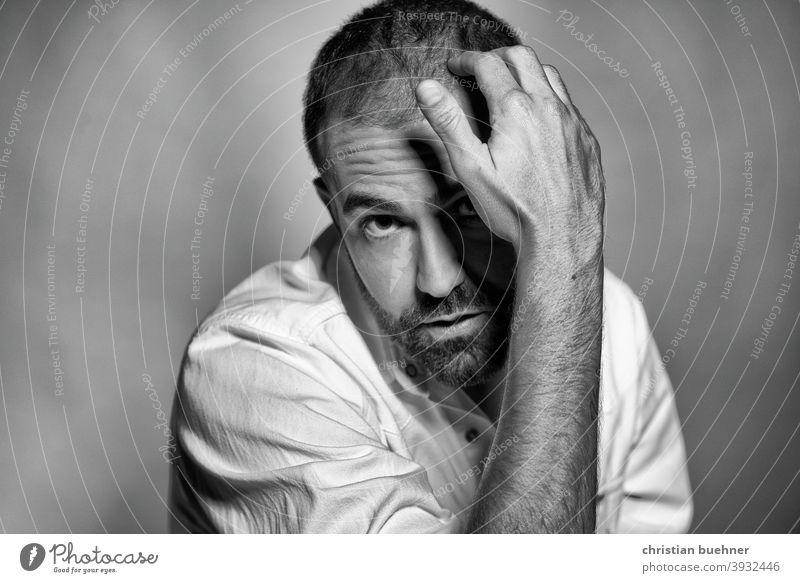 nachdenkliches portrait schwarz weiss mann 30 jahre hand interessant ernst neugierig bart Augenbraue frontal
