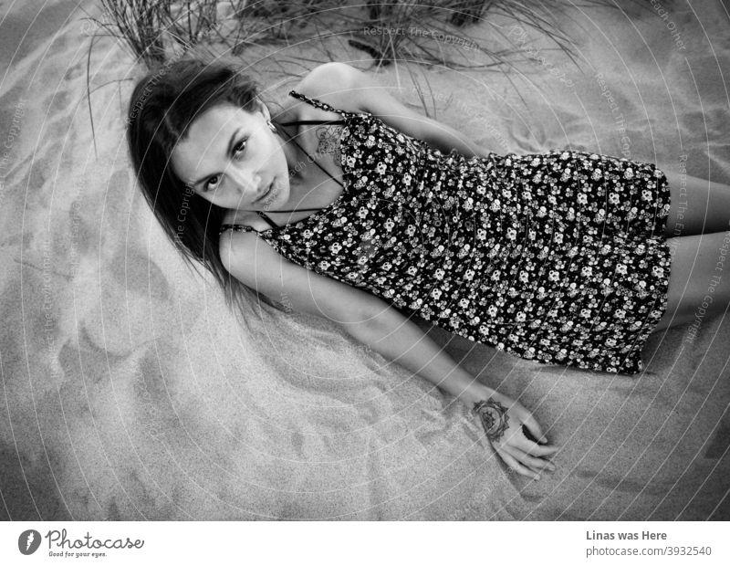 Ein wunderschönes brünettes Modell in einem hellen Kleid liegt auf dem Sand. Auch wenn das Bild schwarz-weiß ist, ist es offensichtlich, dass sie perfekt gebräunt ist, während sie die Sommersonne genießt. Ihre großen schwarzen Augen starren direkt in die Kamera.