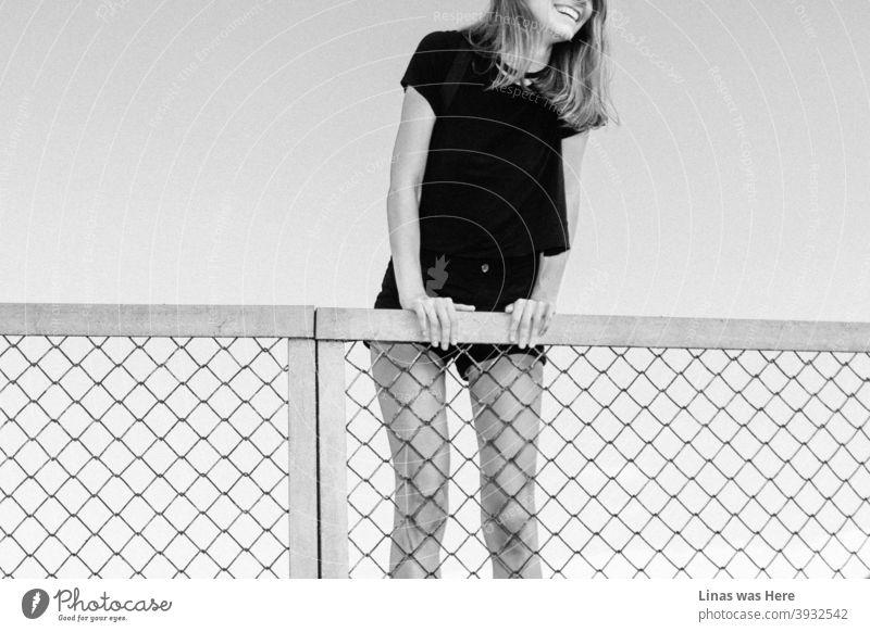 Glückliches Mädchen klettert einen Zaun an einem perfekten Sommertag. Großes Lächeln, lange Beine, und schwarzes Outfit. Ein Rückblick auf wärmere und glücklichere Tage.