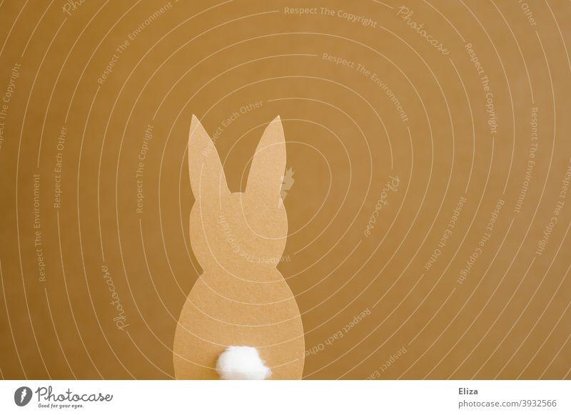 Ein Osterhase aus Papier auf gelbbraunem Hintergrund Scherenschnitt ausgeschnitten basteln Ostern Puschelschwanz Hasenohren Osterdeko
