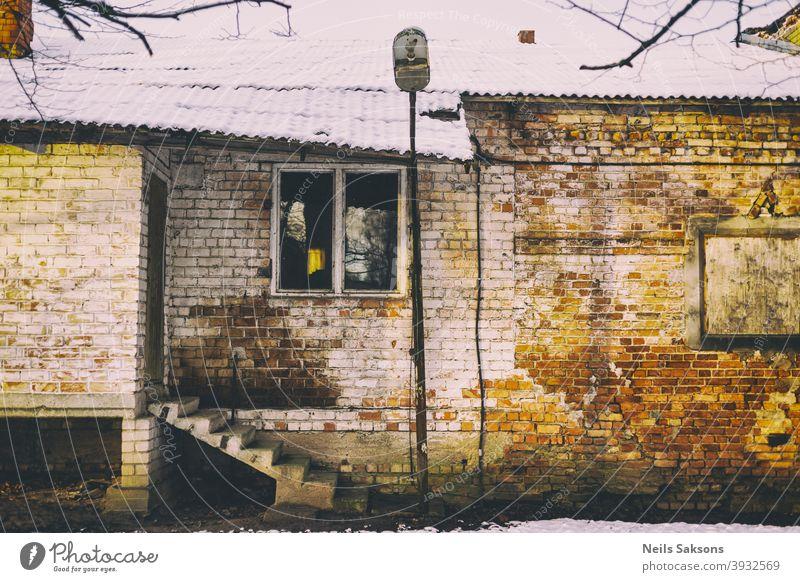 altes Backsteingebäude mit Betontreppe, schiefem, schneebedecktem Dach und alter Laterne gealtert Antiquität Architektur Hintergrund Klotz Baustein braun