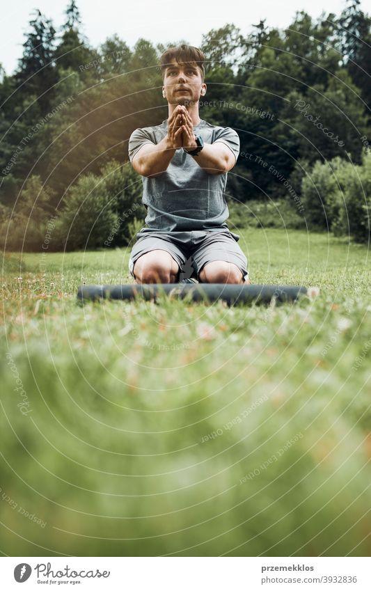 Junger Mann macht Übungen im Freien auf Gras während seiner Calisthenics Workout aktiv Aktivität Athlet sportlich Körper Bodybuilder Bodybuilding calisthenics