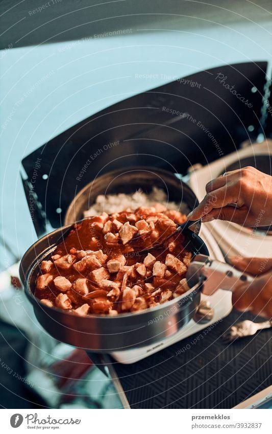 Nahaufnahme von weiblichen Händen setzen Gericht mit Tomatensauce. Frau kochen Mahlzeit auf Elektroherd auf Camping während der Sommerferien Lager Koch Kocher
