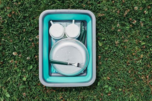 Abwaschschüssel gefüllt mit dem gewaschenen Außengeschirr, Teller, Tassen und Besteck auf den Rasen stellen Lager Camping Campingplatz Reinigen Säuberung Speise