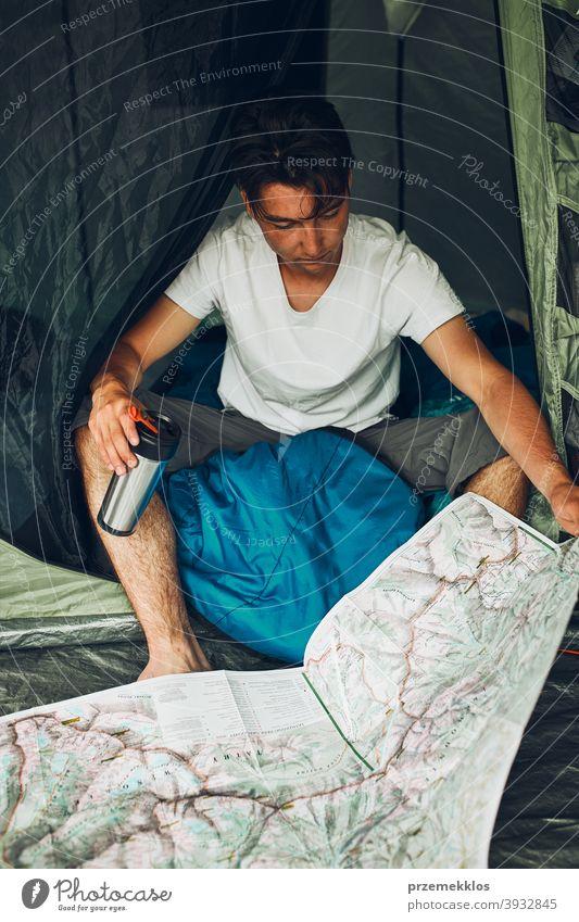 Junger Mann schaut auf eine Karte der Bergwege Planung der nächsten Reise auf Sommerurlaub sitzen in einem Zelt auf Camping Untersuchen Landkarte Tourist reisen