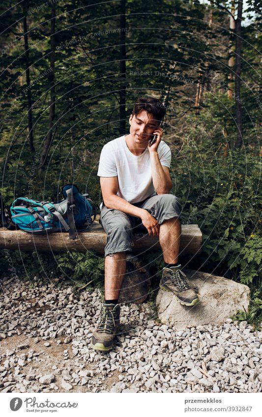 Junger Mann mit Rucksack sprechen am Telefon mit Pause sitzen auf Stamm während der Wanderung in einem Gebirge Aktivität Abenteuer Wald Waldlandschaft Schneise