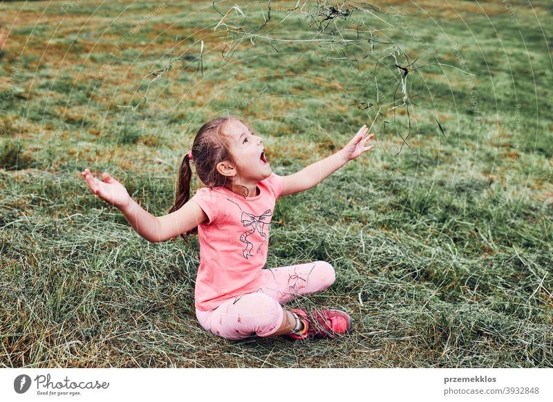 Kleines Mädchen spielt mit Gras genießen Sommertag spielen auf dem Feld während der Ferien Reise Glück Aufregung Genuss Freizeit Urlaub Ausflug Spielen Emotion