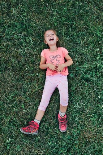 Kleines Mädchen liegend spielen auf Gras genießen Sommertag während Urlaub Reise Glück Aufregung Genuss Freizeit Ausflug Spielen Emotion positiv Lügen Lifestyle