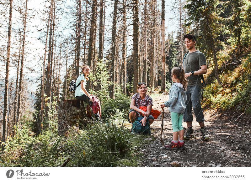 Familie mit Rucksäcken Wandern in einem Gebirge aktiv verbringen Sommerurlaub zusammen Aktivität Abenteuer Frau Wald Waldlandschaft Schneise Freiheit Spaß grün