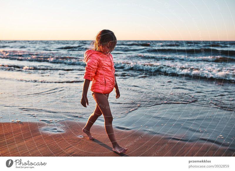 Kleines Mädchen läuft barfuß am Strand bei Sonnenuntergang frei genießen positiv Emotion sorgenfrei Natur im Freien reisen Fröhlichkeit Glück MEER Freude Sommer